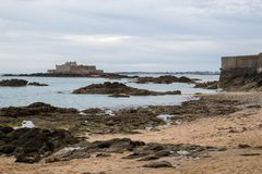 The beach, rocks and Fort National during low tide in Saint Malo. Bretagne, France on a cloudy day in summer stock photos