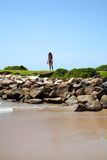 Beach with rocks and girl in background Royalty Free Stock Image