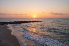 At the beach with rocks jutting out into the sea at the time of sunrise. Or sunset Royalty Free Stock Image