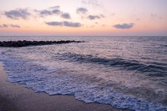 At the beach with rocks jutting out into the sea at the time before sunrise. Or after sunset Stock Photo