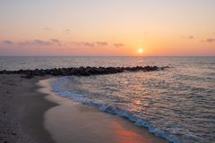 At the beach with rocks jutting out into the sea at the time of sunrise. Or sunset Royalty Free Stock Photos
