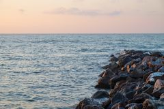 At the beach with rocks jutting out into the sea at the time before sunrise. Or after sunset Royalty Free Stock Photography