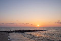 At the beach with rocks jutting out into the sea at the time of sunrise. Or sunset Stock Photo