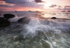 Beach rocks and strong waves. Beach rocks splashed by strong waves during sunset in Kota kinabalu beach, Sabah Borneo royalty free stock photography