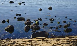 Beach rocks on water stock photography