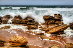 Beach Rocks. Waves crashing against the rocks in Africa royalty free stock photos