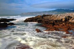 Beach with rocks, waves stream and fog Stock Photography