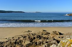 Beach with rocks, wet sand and waves with foam. Blue sky, sunny day, Galicia, Spain. Galicia, La Coruña Province, Rias Altas, Spain. Beach with rocks and royalty free stock photos