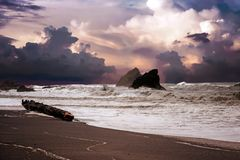 Beach and rocks and wild waves on a cloudy day. Beach and rocks and wild waves on a cloudy rainy day royalty free stock photo