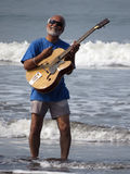 Beach Rockstar. A senior Indian rockstar playing an acoustic guitar in beach waters Royalty Free Stock Images