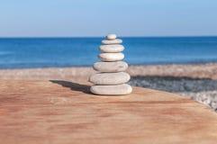 Beach round pebble stone set balance arrangement like zen symbol. On wooden table Royalty Free Stock Photos