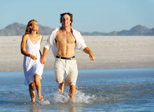 Beach run splash couple Royalty Free Stock Images