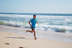 Beach runner. Young man running on the beach royalty free stock photos