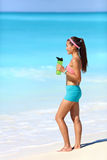 Beach runner taking running break drinking water. Beach runner woman taking running break drinking water standing on white sand. Healthy fit girl wearing stock photography