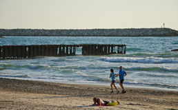Beach running. Couple running on the beach of Tel-Aviv,Israel in sunset Stock Photos