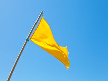Beach safety warning yellow flag with blue sky Stock Photo