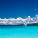 Beach with sailboat in ocean Royalty Free Stock Photos