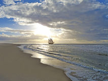 Beach, sailing ship, sea and sunset Stock Photography