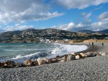 Beach at Salobrena, Andalusia, Spain. Crashing waves onto pebble beach, with larger rocks at Salobrena beach, with backdrop of white village houses Royalty Free Stock Photo