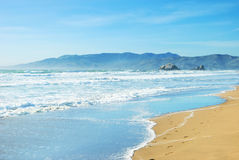 Beach in San Francisco California. With waves coming to the sand and blue sky background Royalty Free Stock Images