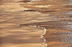 Beach sand background. Beach sand getting wet by the sea water Stock Images