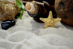 Beach sand, a bottle with a letter inside, seashells and starfish. Stock Photo