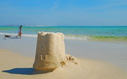 Beach Sand Castle and Dog. Sand castle on seashore with woman walking dog in background Stock Images