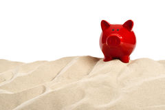 On the Beach - Sand dune with a red  piggy bank in front of a white background - clipping path included Royalty Free Stock Image