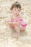 On the beach in the sand little girl sits and plays Stock Photography