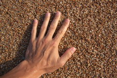 Beach sand and men's arm Royalty Free Stock Photography