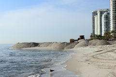 Beach Sand Nourishment Landscaping Coast. Fort Lauderdale, FL, USA - March 3, 2016: Large sand piles distributed on the shores widening the beach. Shore beach Royalty Free Stock Image