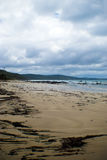 Beach with sand, ocean and an overcast sky Royalty Free Stock Images