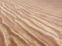 Beach sand pattern closeup, fine rippling sand background. Sand texture royalty free stock photography