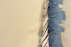 Beach sand protect from wind by wooden wall. Stock Image