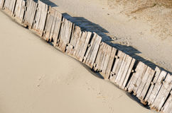 Beach sand protect from wind by wooden wall. Royalty Free Stock Images