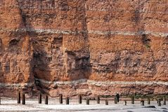 Beach, sand and red cliff Stock Photos