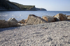 Beach with sand, round stones, selective focus Royalty Free Stock Photos