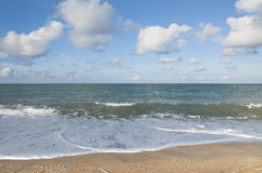 Beach. The Sand, Splashing Waves, Beach, Blue Sky And Clouds Stock Photo