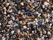 Beach sand stones texture background. Sunset light on beach stones multiforms and colours Stock Image