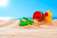 On the Beach - sand toys on a sand dune in front of beautiful azure sea on a sunny day Stock Photos