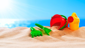 On the Beach - sand toys on a sand dune in front of beautiful azure sea on a sunny day Royalty Free Stock Photography