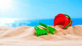 On the Beach - sand toys on a sand dune in front of beautiful azure sea on a sunny day Royalty Free Stock Image