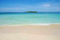 Beach sand with tropical island at the horizon stock images