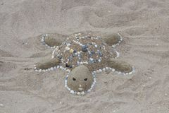 Turtle sand. On a beach sand is a turtle made royalty free stock photo