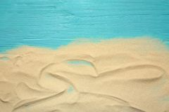 Beach sand on wooden background, top view. With space for text stock photos