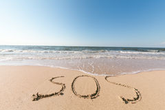 Beach with sand word sos. Sea beach with sand word sos Stock Photography