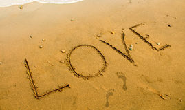Beach sand writing. Romantic seaside photo background or card template. Stock Images
