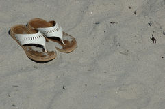 Beach sandals. A pair of sandals sitting in the sand Royalty Free Stock Images
