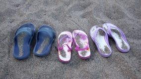 Beach sandals on the dark sand. On a beach near the sea Royalty Free Stock Photo