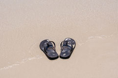 Beach sandals on a sandy beach Royalty Free Stock Image